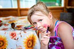 Uma criança com uma escova e pinturas Imagens de Stock Royalty Free