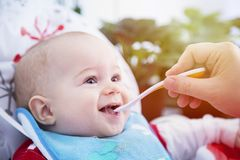 Uma criança come com a colher na tabela fotos de stock