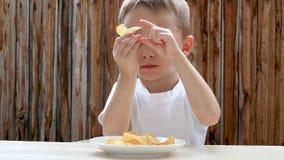 Uma criança come microplaquetas de batata com prazer na perspectiva de uma parede de madeira O menino é satisfeito com o alimento filme