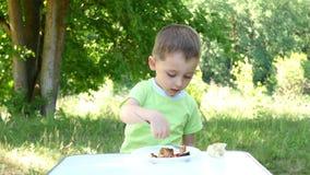 Uma criança come o no espeto, assado com a ketchup de tomate, sentando-se em uma tabela video estoque
