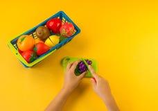Uma criança corta um fruto plástico em uma placa imagens de stock