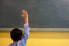 Uma criança da escola na sala de aula na lição imagem de stock