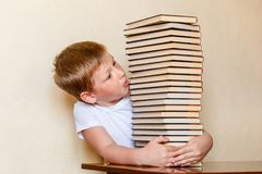 Uma criança de oito anos olha uma grande pilha de livros Povos e livros fotos de stock