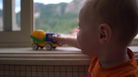Uma criança de pé perto da janela e brincando com o caminhão em câmera lenta vídeos de arquivo