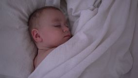 Uma criança de sono bonito que encontra-se sob uma cobertura branca no movimento lento filme