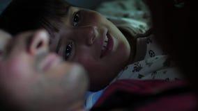 Uma criança e um pai antes das horas de dormir que encontram-se na cama usando um dispositivo video estoque