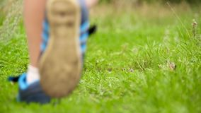 Uma criança em corridas das sapatilhas através da grama verde no movimento lento Pés do close up do bebê filme