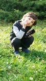 Uma criança em olhares da grama verde na câmera foto de stock
