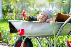 Uma criança em um carrinho de mão fotografia de stock