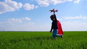 Uma criança em um casaco vermelho e nas corridas da máscara, guardando um plano em sua mão, representando o voo video estoque