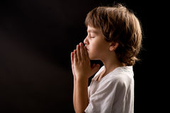 Uma criança em um momento calmo espiritual que praying Imagens de Stock