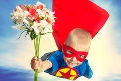 Uma criança em um traje do super-herói com um ramalhete das flores voa a sua mãe amado Imagens de Stock