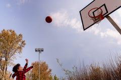 Uma criança entusiástica faz um tiro de basquetebol imagem de stock