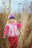 Uma criança está em uma grama seca Fotos de Stock