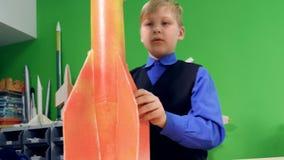 Uma criança está fazendo um modelo de foguete do espaço na escola vídeos de arquivo