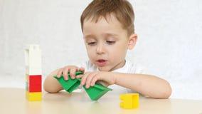 Uma criança está jogando com blocos coloridos, construindo uma casa, sentando-se em uma tabela em um fundo branco Criança e brinq filme