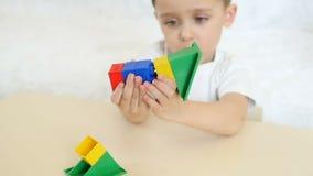 Uma criança está jogando com os blocos coloridos, sentando-se em uma tabela em um fundo branco, no movimento lento vídeos de arquivo