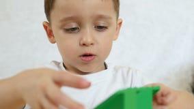 Uma criança está jogando com os blocos coloridos, sentando-se em uma tabela em um fundo branco, no movimento lento, close-up Cria vídeos de arquivo