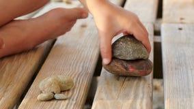 Uma criança está jogando com pedras em uma cremalheira de madeira, close up filme