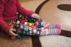 Uma criança está no meio da sala e há muitos brinquedos dispersados ao redor foto de stock royalty free
