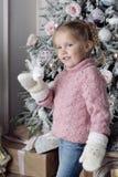 Uma criança está perto de uma árvore de Natal Fotografia de Stock