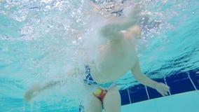 Uma criança está sendo ensinada como nadar filmado debaixo d'água video estoque