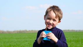 Uma criança feliz bebe o suco de um pacote de papel de um fabricante desconhecido O menino bebe fora O conceito de filme