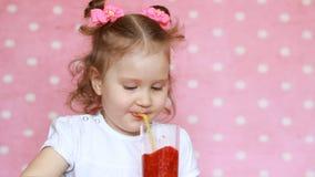 Uma criança feliz bebe um batido da framboesa através de uma palha e ri Retrato do close-up de uma menina bonito que aprecie a vídeos de arquivo