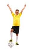 Uma criança feliz com seu pé em uma bola de futebol Uma criança alegre em um uniforme do futebol isolado em um fundo branco espor Imagens de Stock Royalty Free