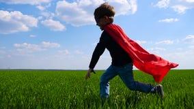 Uma criança feliz em um traje do super-herói em um casaco vermelho corre através do campo verde da esquerda para a direita, press video estoque