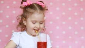 Uma criança feliz está bebendo batidos com uma palha e de um sorriso Retrato do close-up de uma menina bonito que aprecie a video estoque