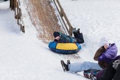 Uma criança feliz está dirigindo para congelar a montanha para a tubulação nas crianças Foto de Stock
