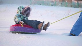 Uma criança feliz monta no snowtube em um movimento lento da neve Paisagem do inverno da neve Fora esportes vídeos de arquivo