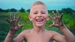 Uma criança feliz mostra suas mãos sujas da terra e dos risos, um menino manchado na lama, um passatempo alegre da infância video estoque