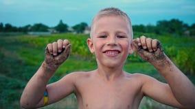 Uma criança feliz mostra suas mãos sujas da terra e dos risos, um menino manchado na lama, um passatempo alegre da infância filme