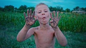 Uma criança feliz mostra suas mãos sujas da terra e dos risos, um menino manchado na lama, um passatempo alegre da infância vídeos de arquivo