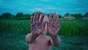 Uma criança feliz mostra suas mãos sujas da terra, um menino manchado na lama, um passatempo alegre da infância video estoque