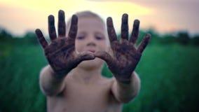 Uma criança feliz mostra suas mãos sujas da terra, um menino manchado na lama, um passatempo alegre da infância filme