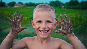 Uma criança feliz mostra suas mãos sujas da terra, um menino manchado na lama, um passatempo alegre da infância vídeos de arquivo