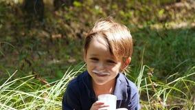 Uma criança feliz nos amores da natureza para beber o kefir de uns produtos láteos de um copo de vidro transparente no movimento  video estoque