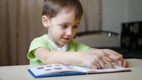 Uma criança feliz que lê um livro com um sorriso, examina as imagens ao sentar-se na tabela em casa vídeos de arquivo