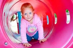 Uma criança feliz que rasteja através de um túnel do jogo. Imagens de Stock