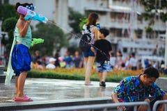 Uma criança joga a água com seu pai durante Songkran foto de stock