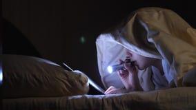 Uma criança lê um livro sob coberturas com uma lanterna elétrica na noite Menino entusiástico vídeos de arquivo