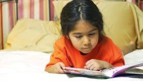 Uma criança latino-americano pequena bonito que encontra-se na cama que lê quietamente video estoque