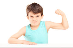 Uma criança louca que mostra seus músculos assentados em uma tabela Imagens de Stock