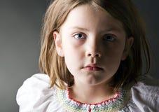 Uma criança loura nova olha a câmera no interesse Fotos de Stock Royalty Free
