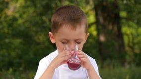 Uma criança na natureza bebe o suco de um copo de vidro O menino gosta de beber uma bebida saudável video estoque