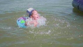 Uma criança nada em um círculo inflável no mar Infância feliz Emoções positivas video estoque