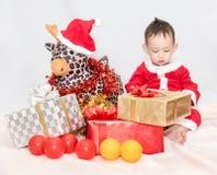 Uma criança no terno vermelho de Santa Claus que senta-se com boneca amo da rena Fotos de Stock Royalty Free